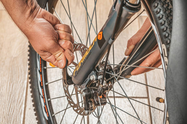 Man fixing a wheel on a bicycle