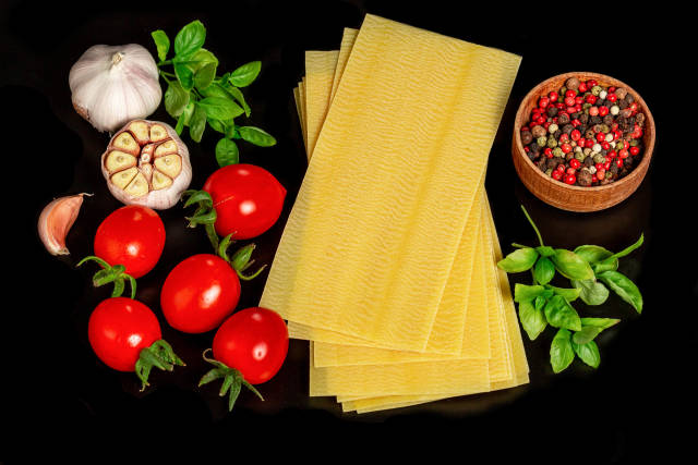 Raw ingredients for lasagna on a black background