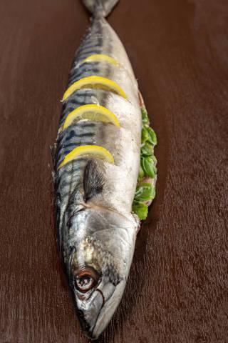 Prepared raw mackerel with basil and lemon for baking