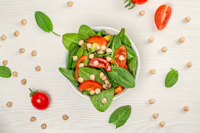 Top view salad with chickpeas and tomatoes on white wooden background