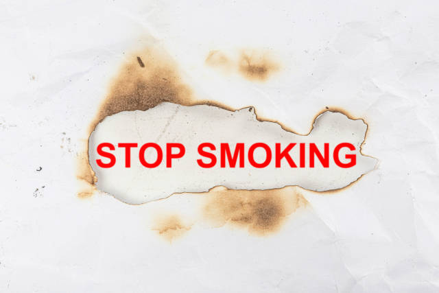 Stop smoking - red lettering in a burnt paper frame