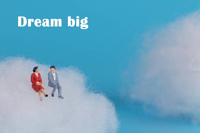 Couple sitting on a cloud with Dream Big text