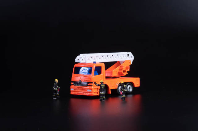 Ladder fire engine with miniature firefighters