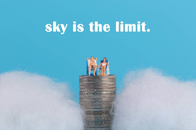Couple sitting on top of a coinstack surrounded with clouds and Sky is the limit text