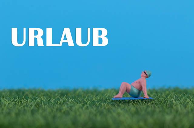 Miniature man relaxing on green grass with Urlaub text