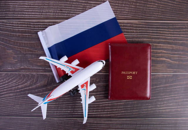 Passport, miniature airplane and flag of Russia on wooden table