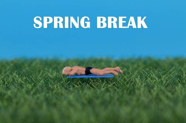 Miniature man relaxing on green grass with Spring Break text