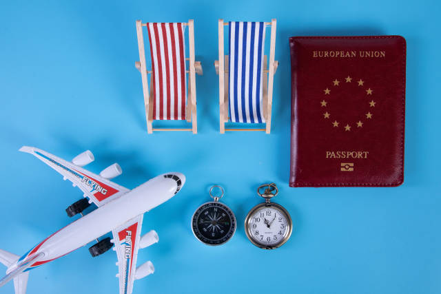 Small airplane, passport and beach chairs on blue background