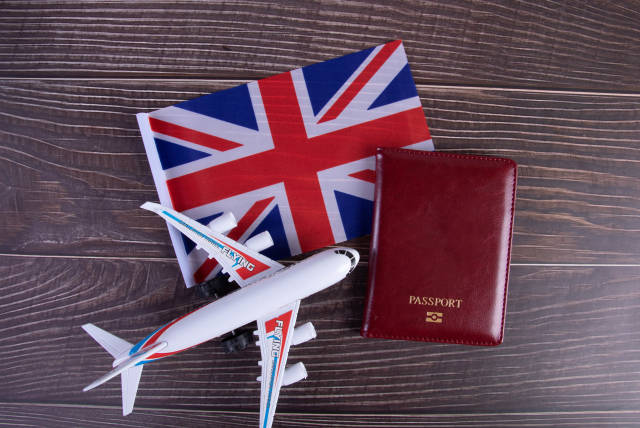 Passport, miniature airplane and flag of United Kingdom on wooden table