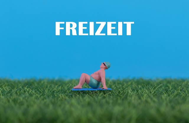 Miniature man relaxing on green grass with Freizeit text