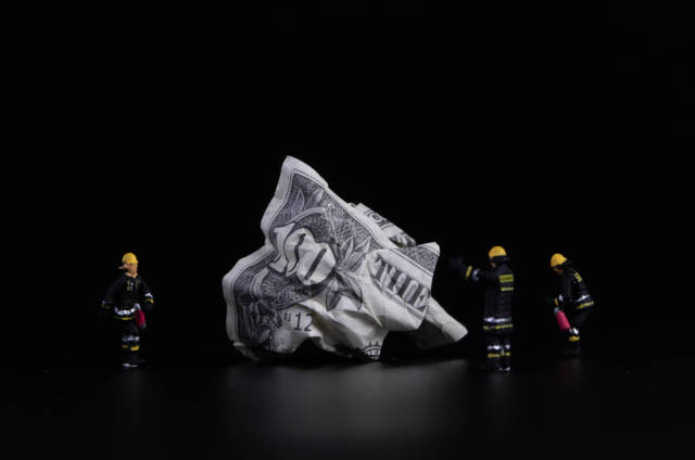 Crushed 100 dollar banknote with miniature firefighters on black background
