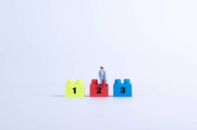 Miniaturausgabe eines Mannes sitzt auf einem Plastikblock