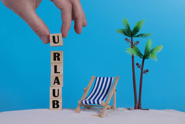 Hand with wooden blocks wiht Urlaub text and beach chair on blue background