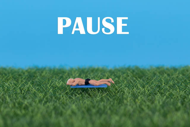 Miniature man relaxing on green grass with Pause text