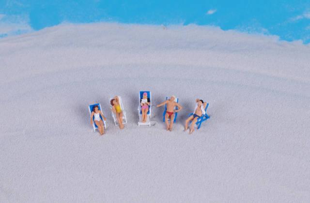 Miniature people at sandy beach