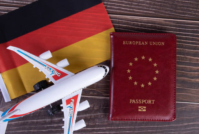 Passport, miniature airplane and flag of Germany on wooden table