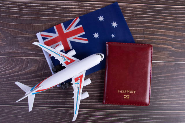 Passport, miniature airplane and flag of Australia on wooden table