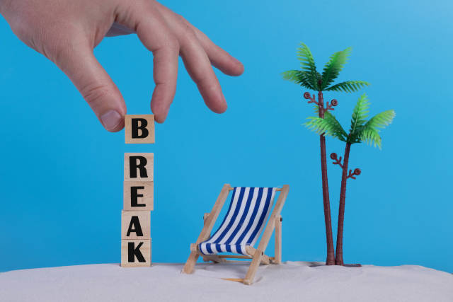 Hand with wooden blocks wiht Break text and beach chair on blue background