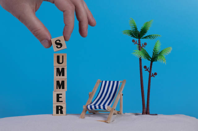 Hand with wooden blocks wiht Summer text and beach chair on blue background