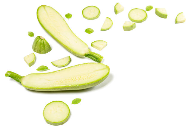 Halves and sliced zucchini on white background