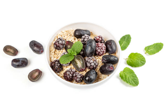 Oatmeal with blueberries, grapes and mint on a white background