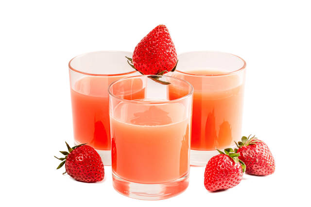 Three glasses of juice and ripe strawberries