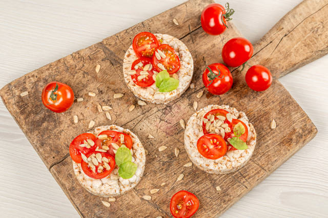 Diet food concept, rice breads with tomato, sunflower seeds and basil, top view