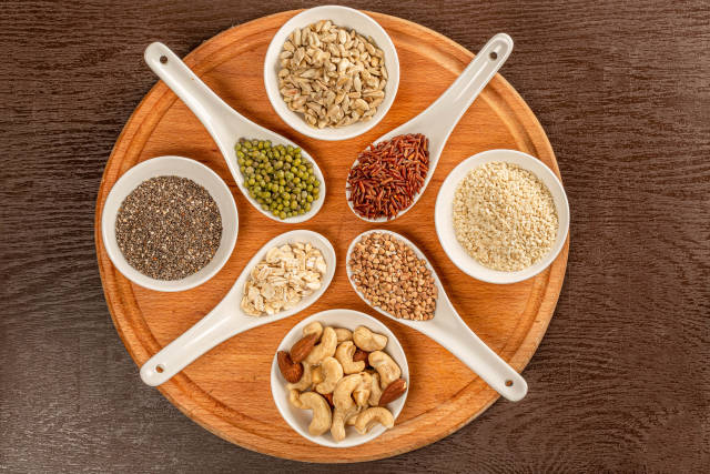 Top view of nuts and seeds in bowls and grains of cereals in spoons on round wooden board
