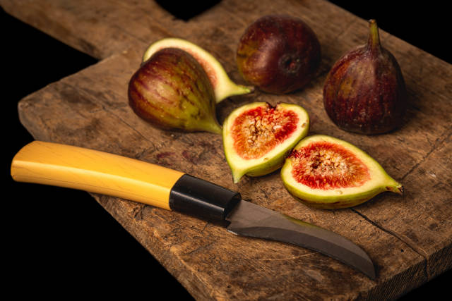 Raw fresh figs on vintage wooden board with knife