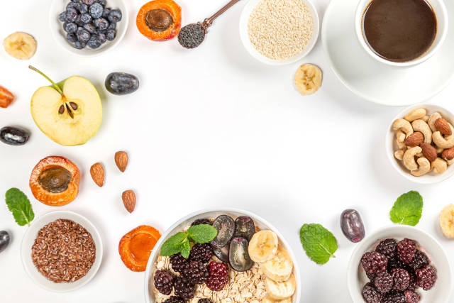 Frame with coffee, oatmeal, fruit, nuts and seeds on white with free space, top view