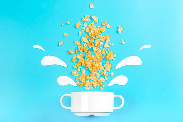 Breakfast background with scattered cornflakes on a blue background