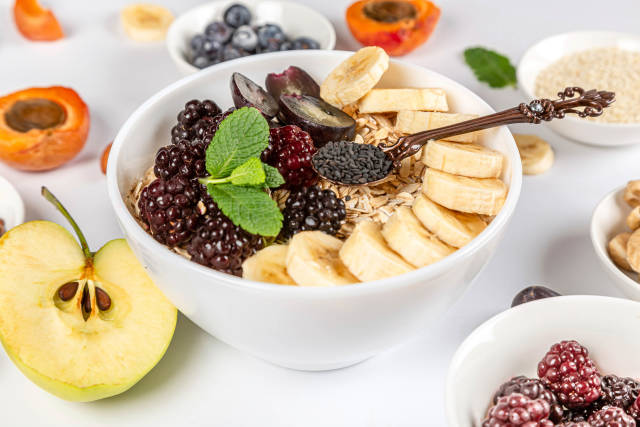 Close-up, a bowl of oatmeal with banana, berries and black sesame seeds