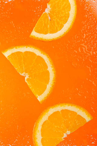 Slices of ripe orange on an orange background with water drops