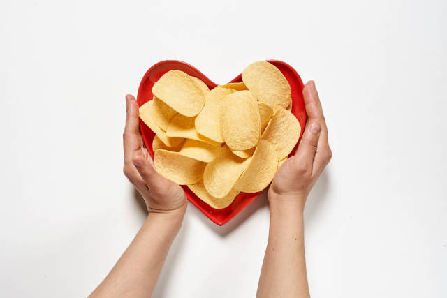 Hands hold heart-shaped plate full of crispy salty chips