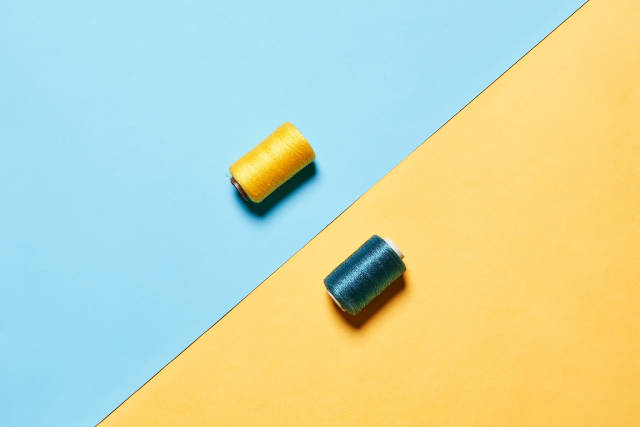 Two colorful spools on colored paper background