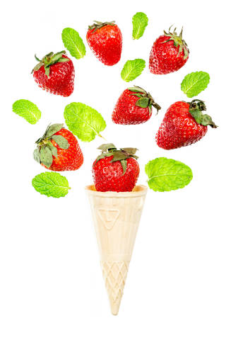 Waffle cone with strawberries and mint leaves on white