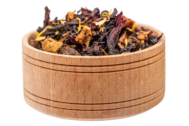 Dry tea with hibiscus and dried fruits in a wooden bowl on a white background