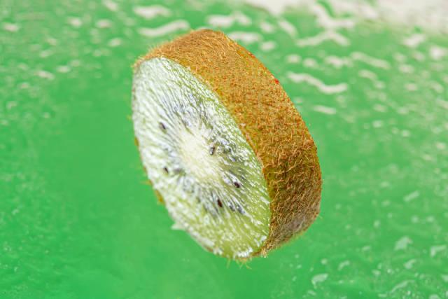 Slice of ripe kiwi on a green background
