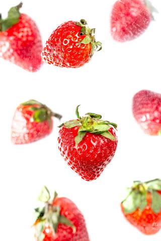 Ripe red strawberries falls, white background