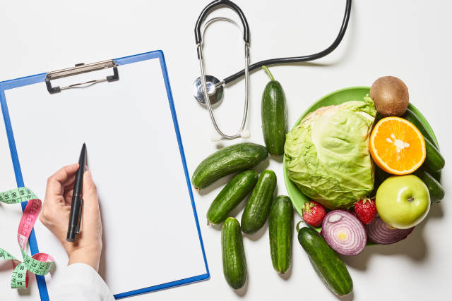 A dietician writing healthy dieting prescriptions on the paper
