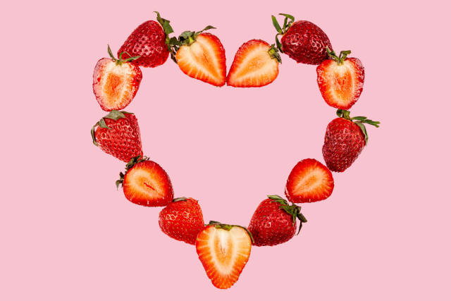 Heart made of halves of strawberries on a pink background, top view