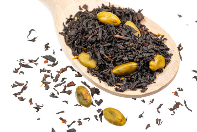 Wooden spoon with dried black tea and green seeds