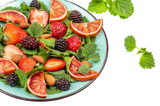 Fresh salad with fruits and almonds, close up