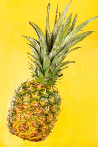 Whole sweet fresh pineapple on yellow with water drops