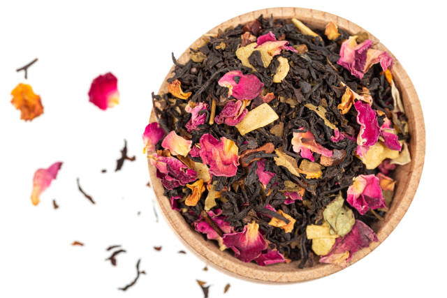 Dry black tea with rose petals in a wooden bowl, top view
