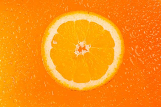 Round orange slice with water drops on orange background