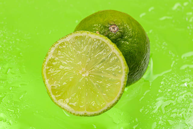 Ripe lime on a green background with water drops