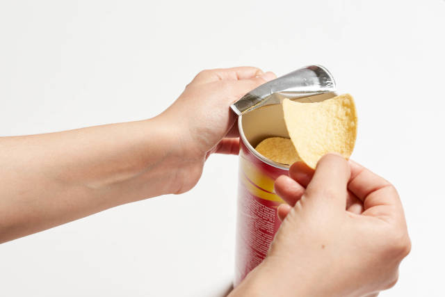 Hands taking out and eating chips