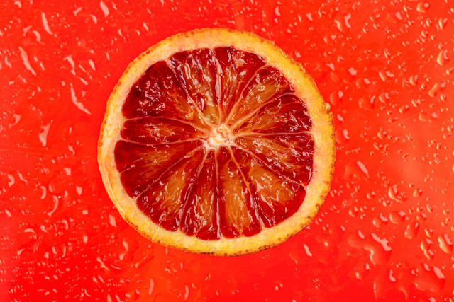 Section of ripe sicilian orange on red background with drops