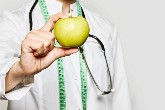 Healthy life, Dieting concept. A doctor hand holds an apple